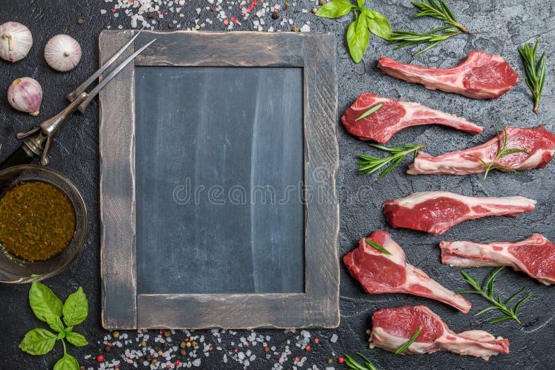 Сырцовые отбивные котлеты овечки с солью, перцем, розмариновым маслом стоковое фото