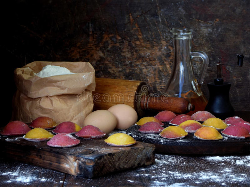 Сырцовые розовые желтые вареники или равиоли свеклы заполненные с сыром рикотты на деревянной доске на темной предпосылке Космос  стоковая фотография