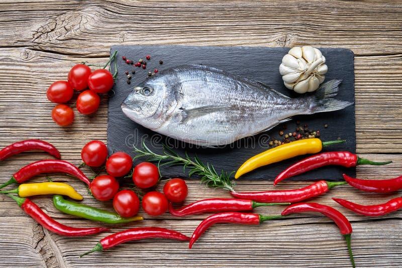 Сырцовые рыбы dorada на черной разделочной доске шифера с aro овощей стоковые фото