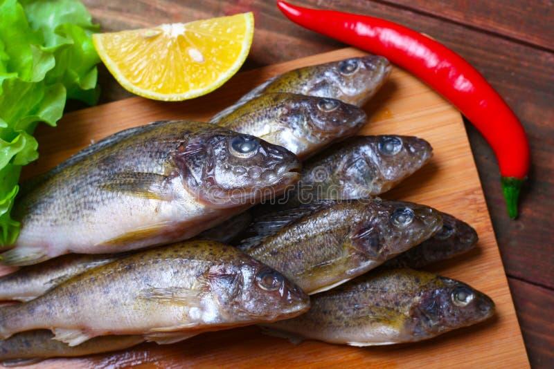 Сырцовые рыбы ruff redfish на кухонном столе с овощами и лимоном стоковая фотография rf