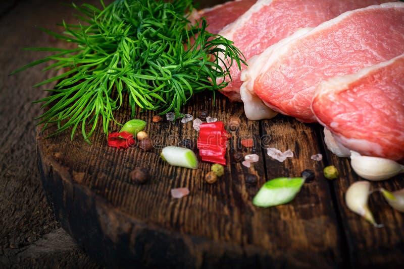 Сырцовые сочные стейки мяса готовые для жарить в духовке на черной доске мела Филе с томатами вишни, горячим перцем и травами Кос стоковое изображение rf