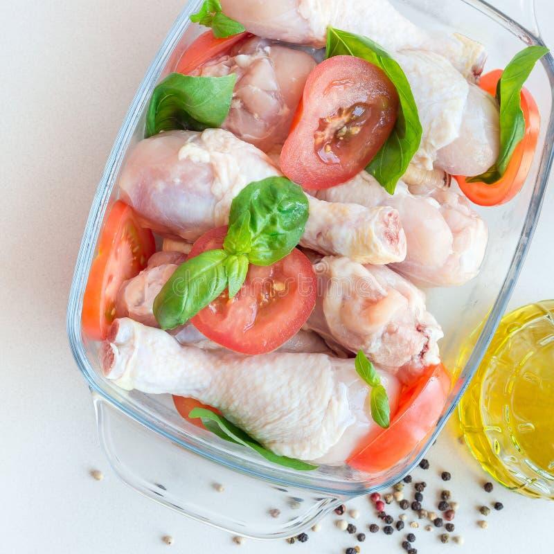 Сырцовые сырые куриные ножки, drumsticks с томатами и базилик в стеклянном подпирая блюде, квадрат, взгляд сверху стоковое фото rf