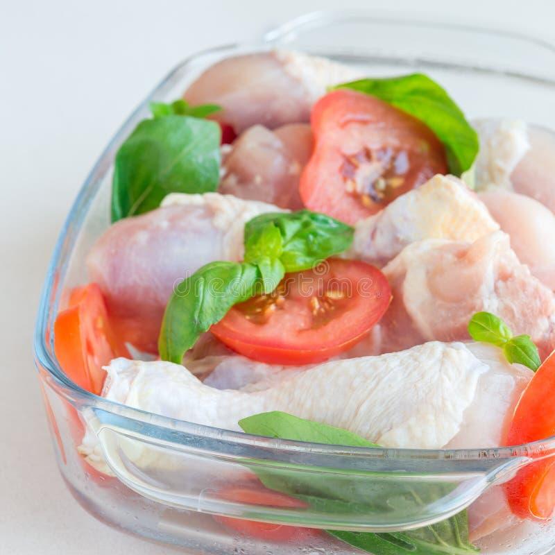 Сырцовые сырые куриные ножки, drumsticks с томатами и базилик в стеклянном подпирая блюде, квадратном формате стоковые изображения rf
