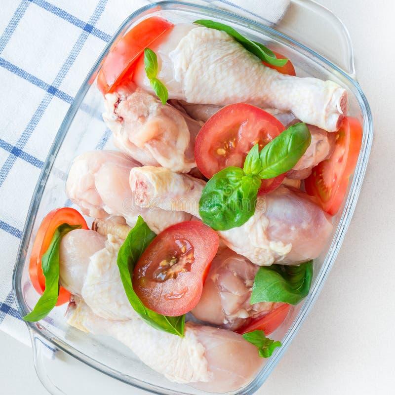 Сырцовые сырые куриные ножки, drumsticks с томатами и базилик в стеклянном подпирая блюде, квадратном формате, взгляде сверху стоковая фотография rf