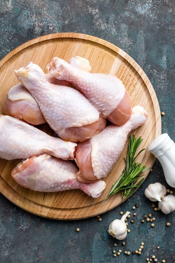 Сырцовые сырые ноги цыпленка, drumsticks на деревянной доске, мясе с ингридиентами для варить стоковые изображения rf