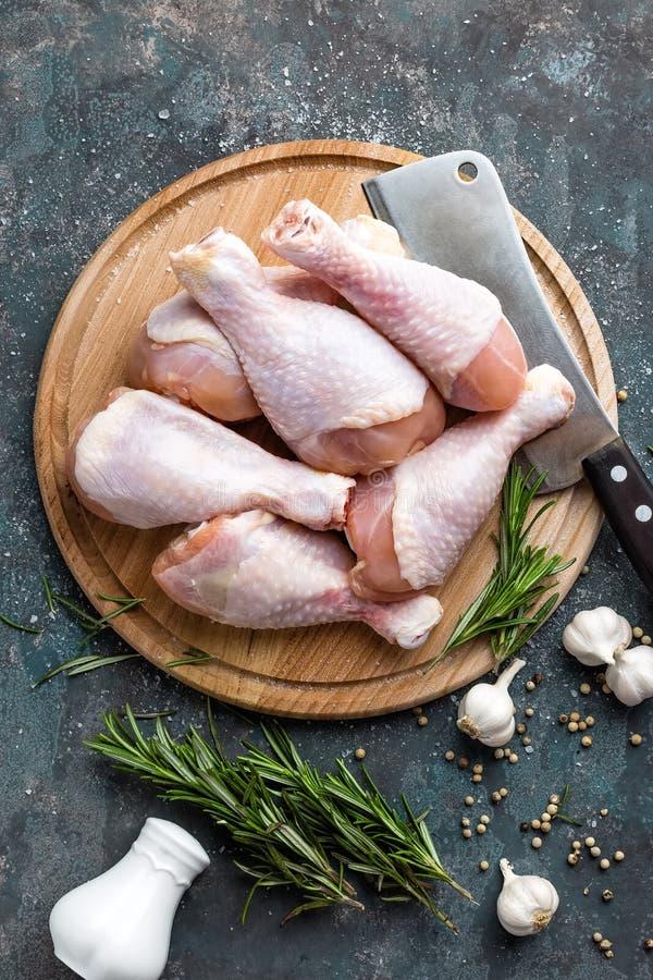Сырцовые сырые ноги цыпленка, drumsticks на деревянной доске, мясе с ингридиентами для варить стоковые фотографии rf