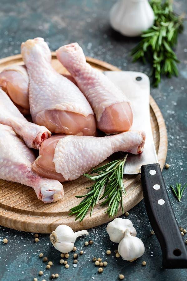 Сырцовые сырые ноги цыпленка, drumsticks на деревянной доске, мясе с ингридиентами стоковое изображение