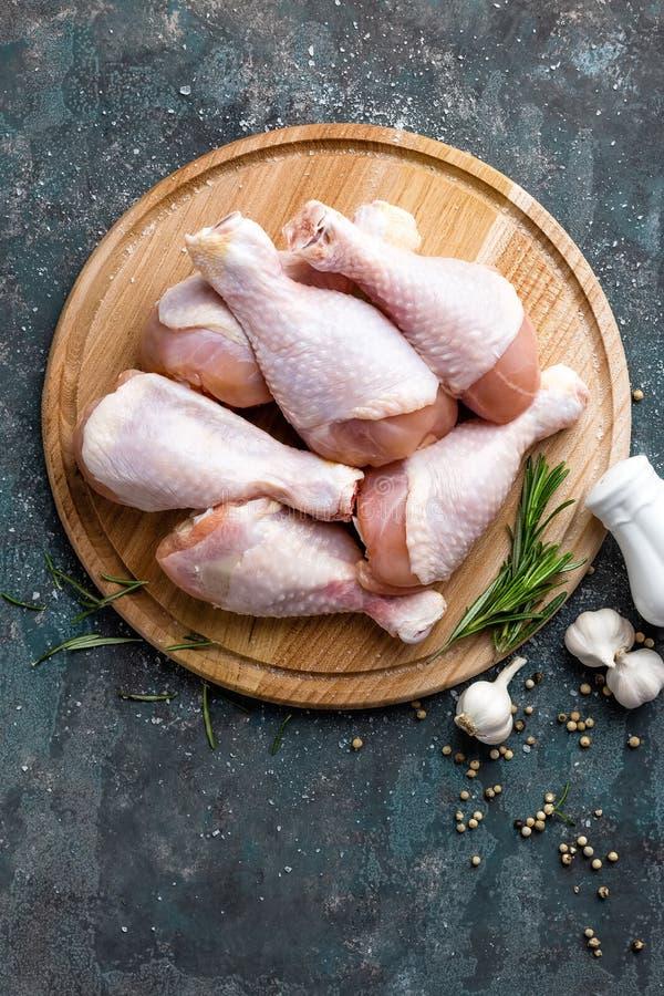 Сырцовые сырые ноги цыпленка, drumsticks на деревянной доске, мясе с ингридиентами для варить стоковое фото