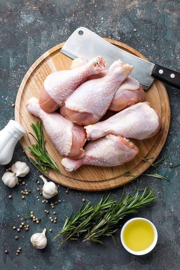 Сырцовые сырые ноги цыпленка, drumsticks на деревянной доске, мясе с ингридиентами для варить стоковая фотография