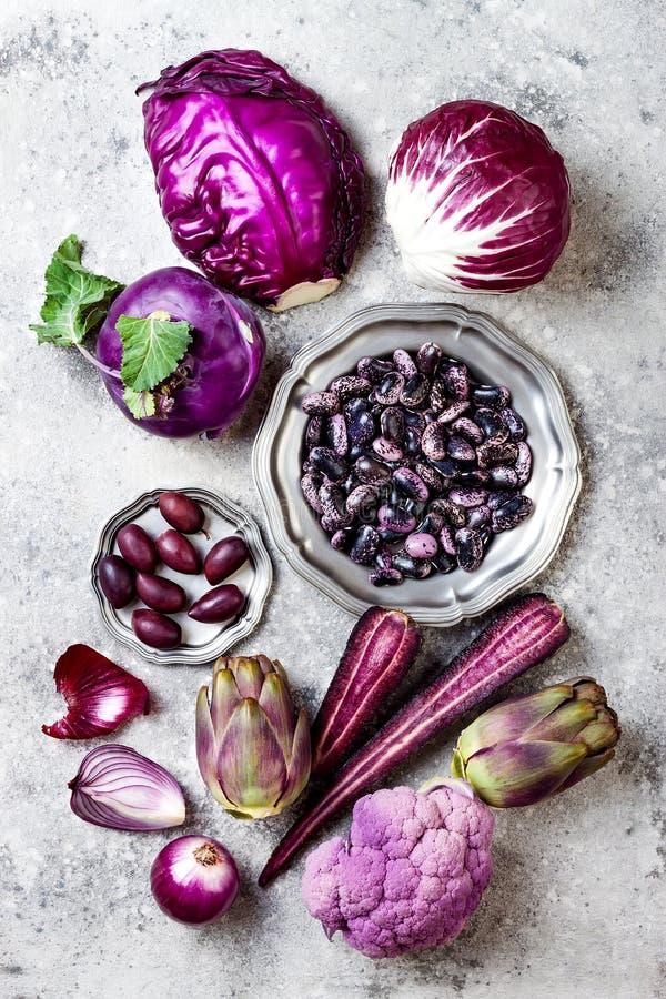 Сырцовые фиолетовые овощи над серой конкретной предпосылкой Капуста, салат radicchio, оливки, кольраби, морковь, цветная капуста стоковые фото