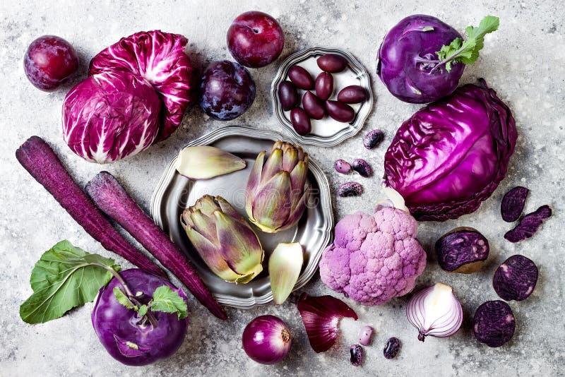 Сырцовые фиолетовые овощи над серой конкретной предпосылкой Капуста, салат radicchio, оливки, кольраби, морковь, цветная капуста стоковые изображения