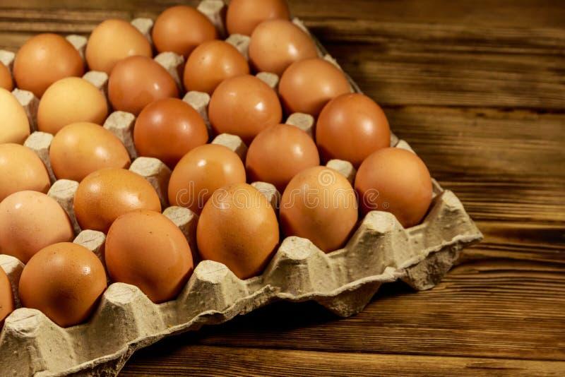 Сырцовые яйца цыпленка в пакете картона на деревянном столе стоковые изображения