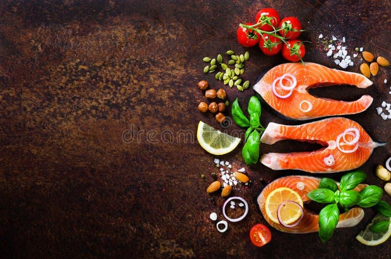 Сырцовые salmon стейки, ароматичные травы, лук, лимон, соль и свежие овощи для варить на деревянной предпосылке Copyspace стоковое фото rf