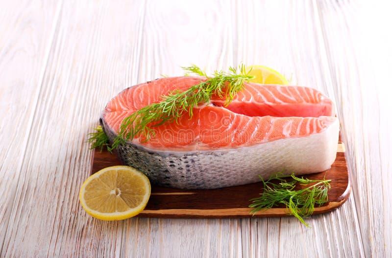 Сырцовые salmon стейки рыб на разделочной доске стоковое фото