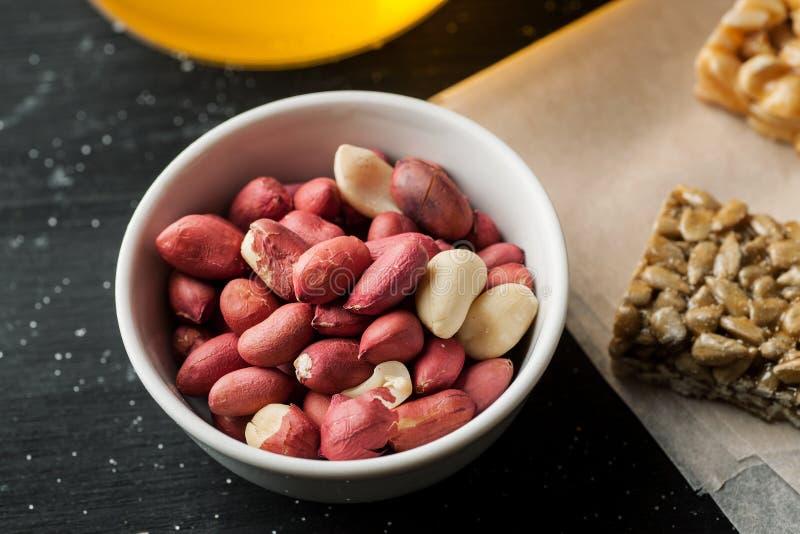 Сырцовые unpeeled арахисы в белом керамическом шаре на черном деревянном столе стоковые фотографии rf