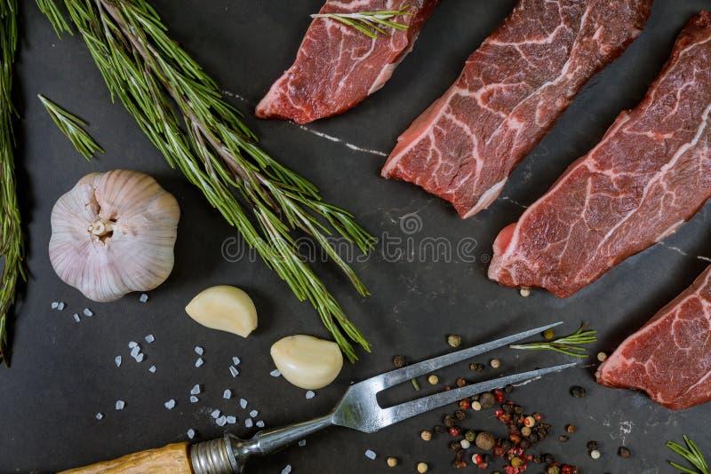 Сырцовый бифштекс с приправами, черная предпосылка, взгляд сверху стоковые изображения