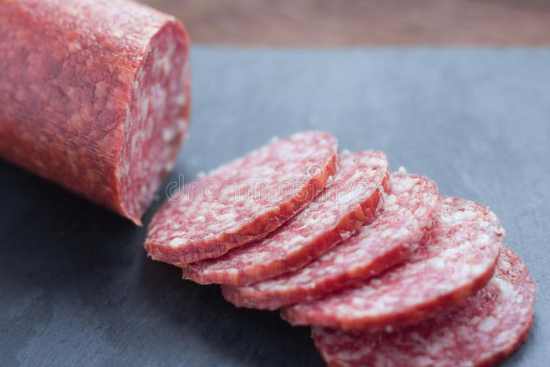 Сырцовый копченый отрезок сосиски на таблице стоковые изображения