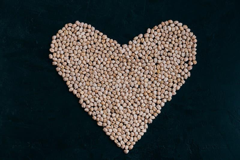 Сырцовый нут в форме сердца изолированной на черном bacground Выросли органическое, который Сырцовый протеин Ингредиент Vegan здо стоковые фото