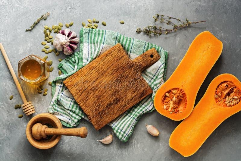 Сырцовый сквош тыквы или butternut, пустая разделочная доска, травы, мед на серой предпосылке r стоковые фотографии rf