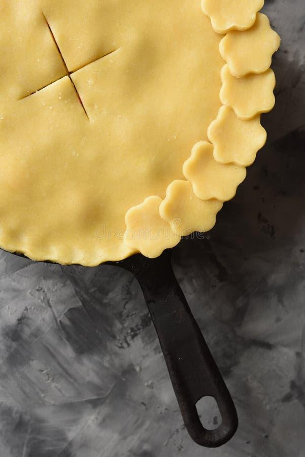 Сырцовый старомодный пирог ягоды в лотке литого железа на темном конкретном космосе экземпляра взгляда сверху предпосылки Низкий  стоковое изображение rf