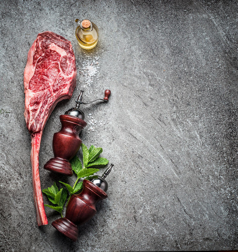 Сырцовый стейк говядины томагавка, подготовка для гриля или варить на темной деревенской конкретной предпосылке, взгляд сверху стоковая фотография rf