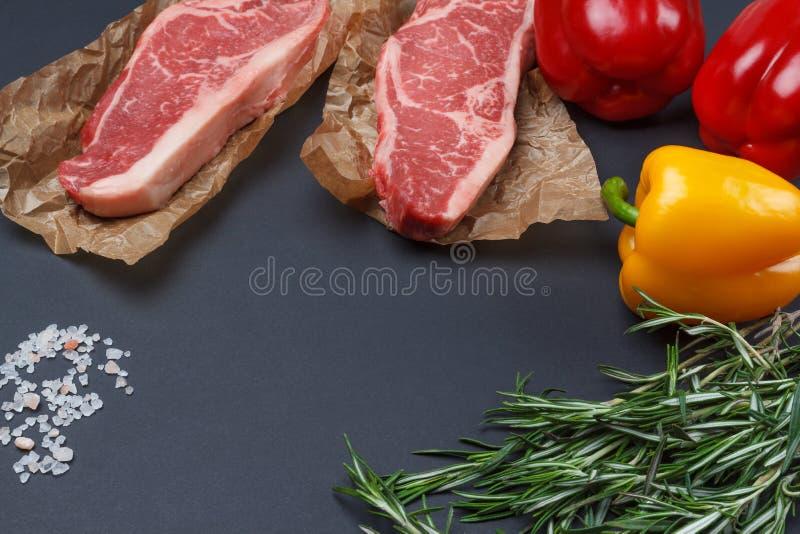 Сырцовый стейк Нью-Йорка с предпосылкой сладостного перца, розмаринового масла и соли стоковое фото rf