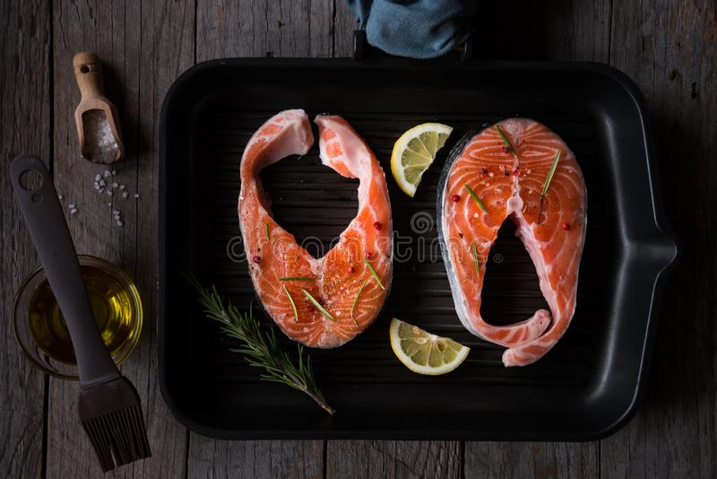 Сырцовый стейк семг, сырые рыбы с розмариновым маслом, лимон и специи на черноте стоковые изображения