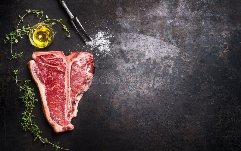 Сырцовый стейк T-косточки с свежими травами и масло на темной ржавчине metal предпосылка, взгляд сверху стоковое изображение