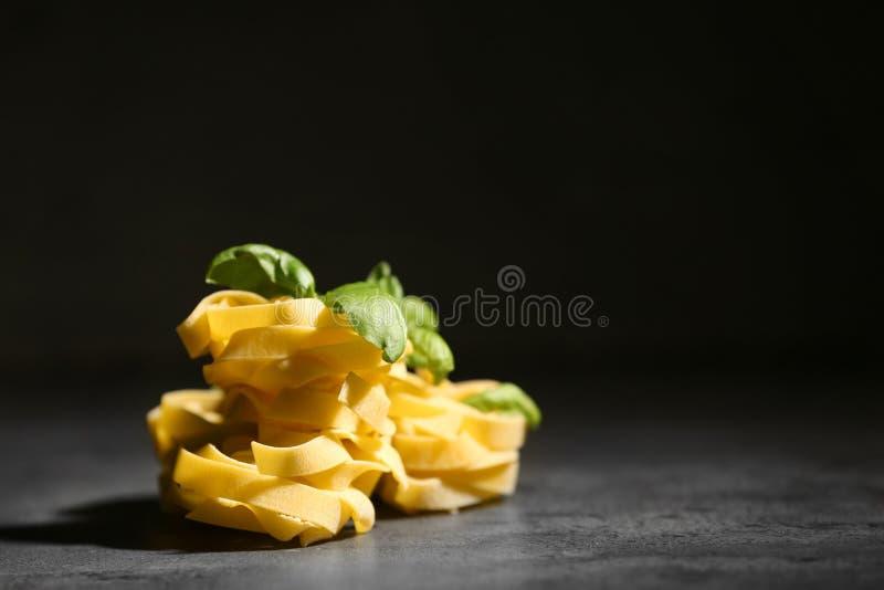 Сырые макаронные изделия fettuccine на таблице против темной предпосылки стоковые фотографии rf