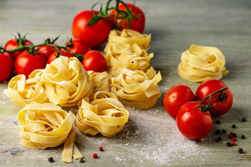Сырые макаронные изделия fettuccine с томатами стоковые изображения rf