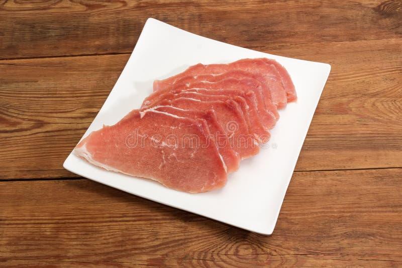 Сырые размороженные куски свинины на квадратном блюде стоковые фотографии rf