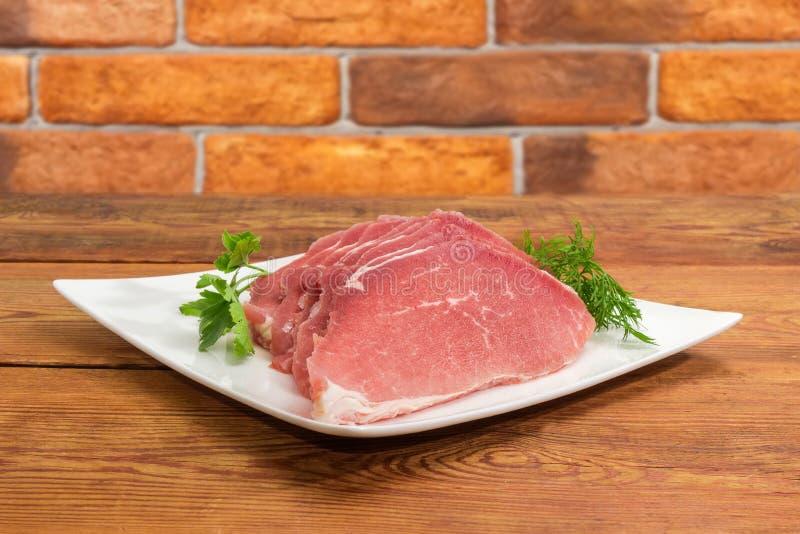 Сырые размороженные куски свинины с зелеными цветами на квадратном блюде стоковые изображения rf