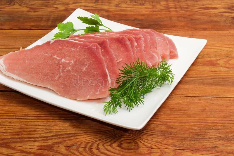 Сырые размороженные куски свинины с зелеными цветами на квадратном блюде стоковые фото