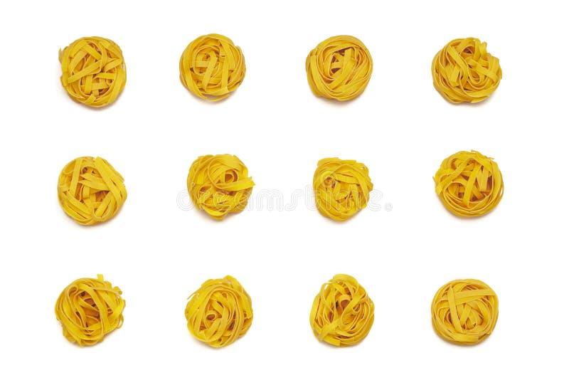 Сырые свернутые традиционные итальянские макаронные изделия на белой изолированной предпосылке, Часть сырцовых fettuccine или tag стоковые фотографии rf