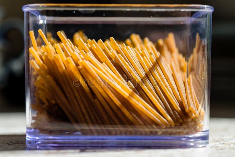 Сырье дурум спагетти внутри пластикового контейнера на домашней кухне стоковые фотографии rf