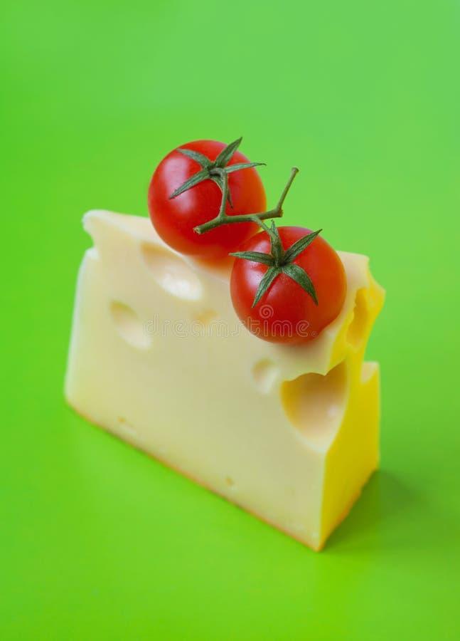 Сыр и томаты на зеленом цвете стоковое изображение rf