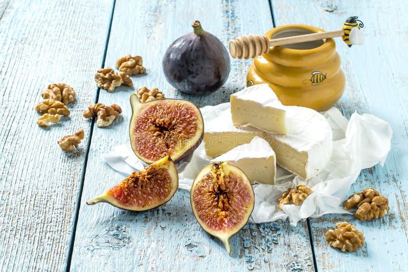 Сыр камамбера, зрелые смоквы, мед и грецкие орехи стоковое изображение