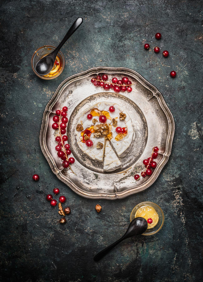 Сыр камамбера служил на серебряном диске с ягодами и медом стоковое изображение