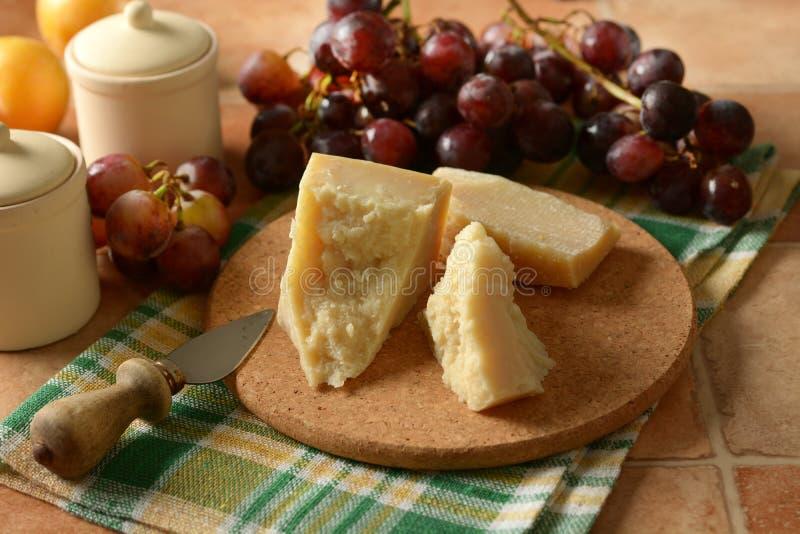 Сыр пармесан на таблице с связкой винограда стоковая фотография rf