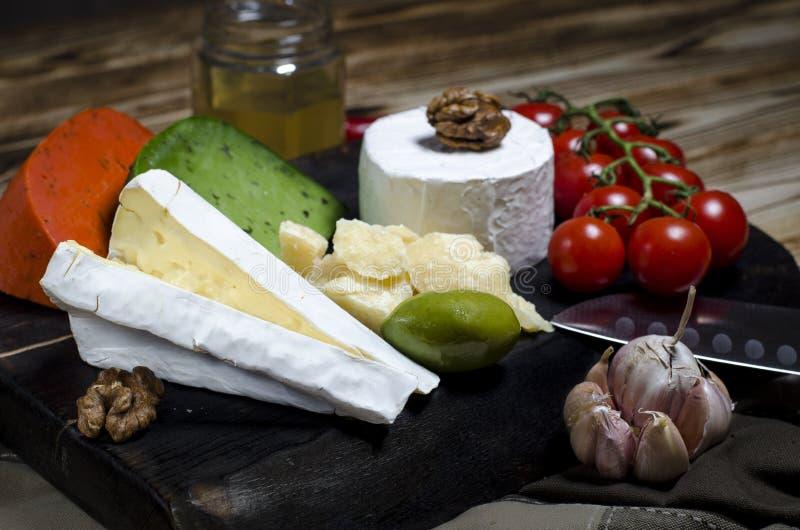 Сыр смешивания на темной предпосылке на деревянной доске с виноградинами, медом, гайками, томатами и базиликом r стоковые фото
