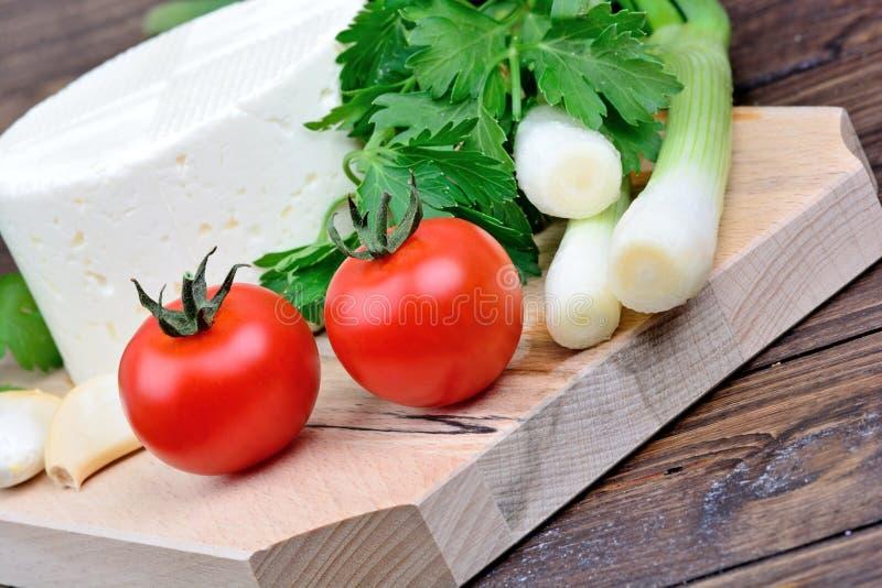 Сыр с овощем на прерывать деревянную доску стоковые фотографии rf