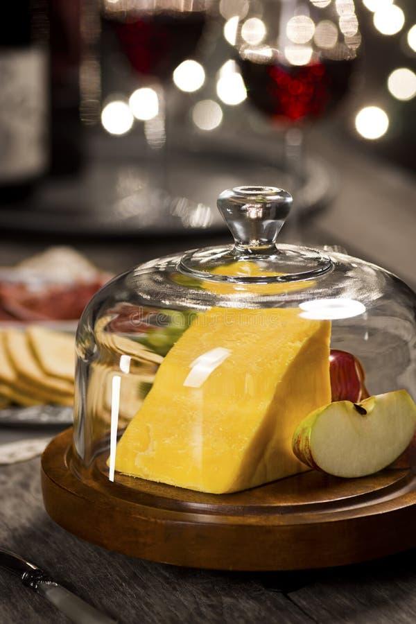 Сыр чеддера под стеклянным куполом на партии праздника стоковые изображения