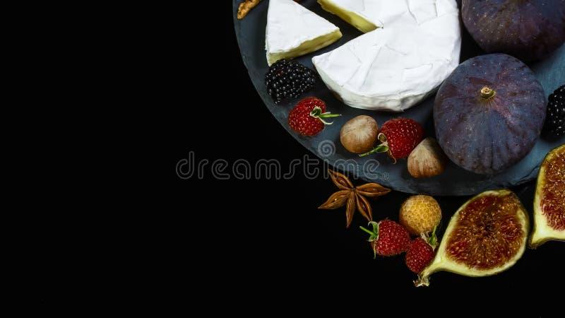 Сыр Camembert с инжиром и ягодами на старом черном деревянном столе еда для вина и романтическая, сыр деликатесен Область текста стоковые изображения