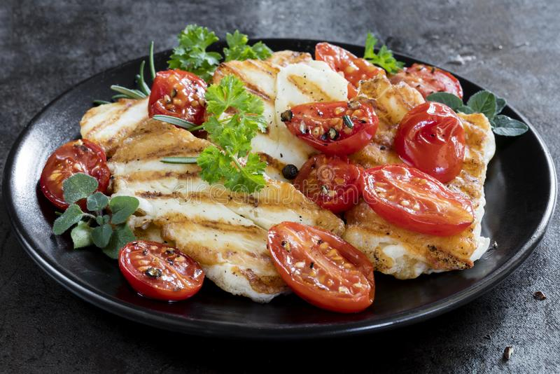 Сыр Halloumi с зажаренными в духовке томатами и травами вишни стоковое изображение rf