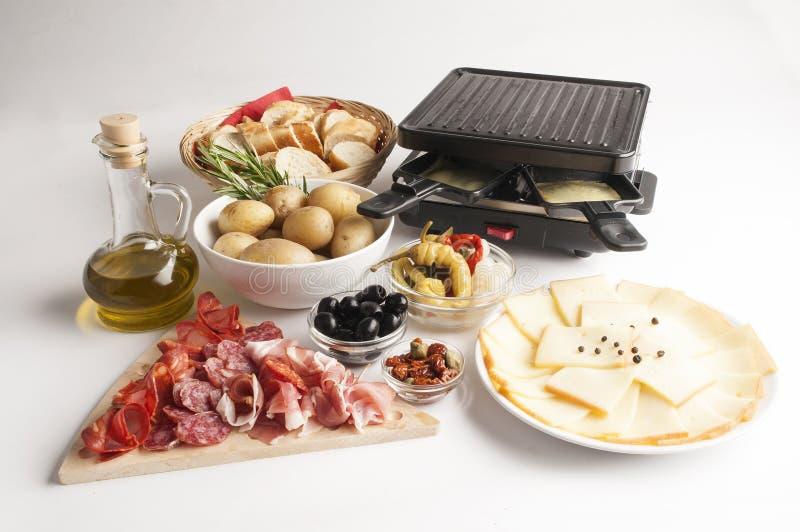Сыр Raclette установил на белую предпосылку с мясом и сосисками стоковая фотография
