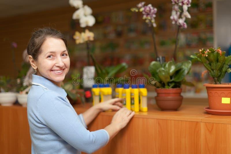 Сь возмужалая женщина выбирает землеудобрение в бутылке на саде s стоковые фото