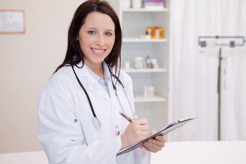 Сь женский врач принимая примечания стоковое фото