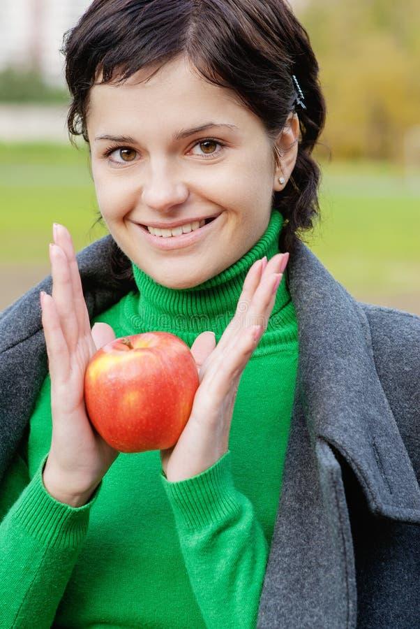 Сь милая женщина сдерживает зрелое яблоко стоковое фото rf
