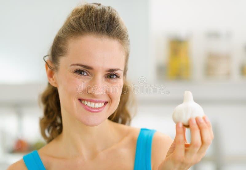 Сь молодая домохозяйка показывая чеснок стоковые фото