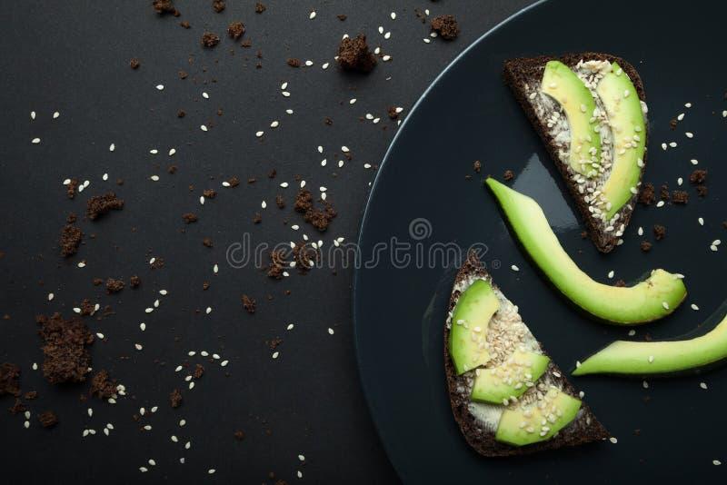 Сэндвич авокадоа на темном хлебе рож, сделал из свежего отрезанного авокадоа с расплавленными сыром и сезамом Взгляд сверху на че стоковое фото rf